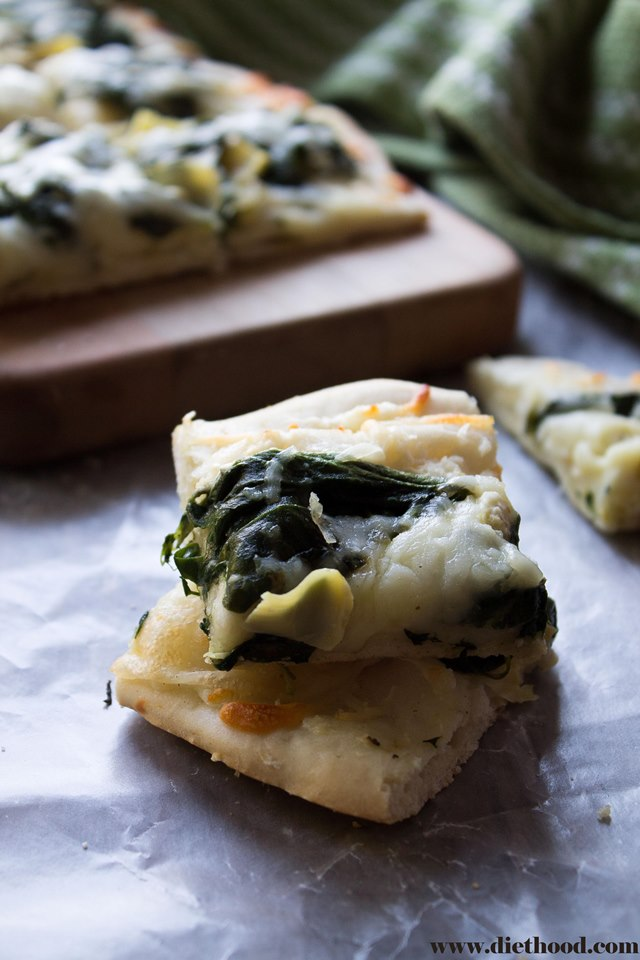Delicious homemade pizza crust topped with spinach, cream cheese, and artichokes.